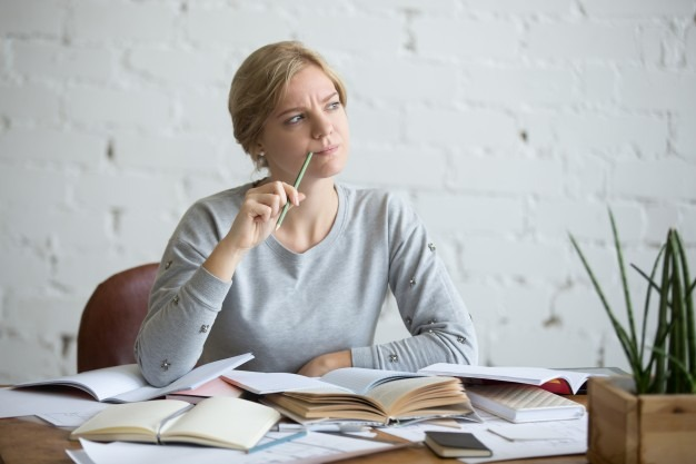 Portrait of a student woman at the desk, frowned Free Photo